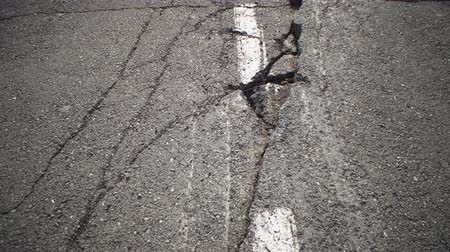 dividing : Camera moves along deep cracks in asphalt with white dashed marking line. View of fault in road, consequences of natural disaster, earthquake or man-made disaster.