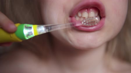 general electric : Close-up of cute blonde child brushing her teeth.Toothbrush glows with lights, helping kid to see every baby tooth in mouth. Concept of oral hygiene and healthy lifestyle. Stock Footage