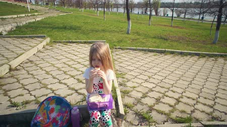 shoarma : Blonde little girl eating lunch in park on sunny day.She holds reusable container of food on her lap, next to colorful backpack and bottle of water. Happy child sitting on step and bites off shawarma. Stockvideo