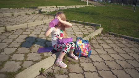 reutilizável : Blonde little girl eating lunch in park on sunny day.She holds reusable container of food on her lap, next to colorful backpack and bottle of water. Happy child sitting on step and bites off sandwich.