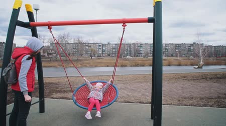 編まれた : Young mother swings happy daughter on round seesaw nets in park on cloudy day, slow motion. Family is dressed in warm clothes and hats, they have fun together.