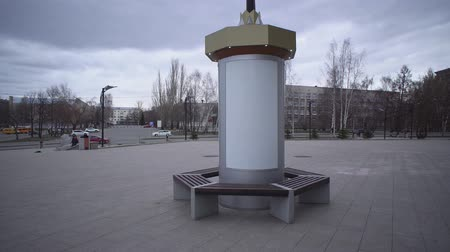 nem városi színhely : Handheld shot of round blank mockup poster of street advertising column stand on sidewalk in grey cloudy day. Stock mozgókép