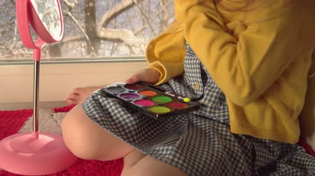 hardal : Little cute girl in a mustard jacket and a blue bandage puts makeup looking in a pink mirror, she sits on the windowsill, outside the window is a winter landscape. A child prepare for a carnival. Stok Video