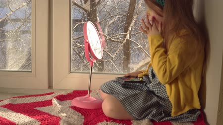 mustard : Little cute girl in a mustard jacket and a blue bandage puts makeup looking in a pink mirror, she sits on the windowsill, outside the window is a winter landscape. A child prepare for a carnival. Stock Footage