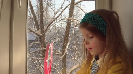 mustár : Little cute girl in a mustard cardigan and a blue bandage puts makeup looking in a pink mirror, she sits on the windowsill, outside the window is a winter landscape. A child learns to use cosmetics. Stock mozgókép