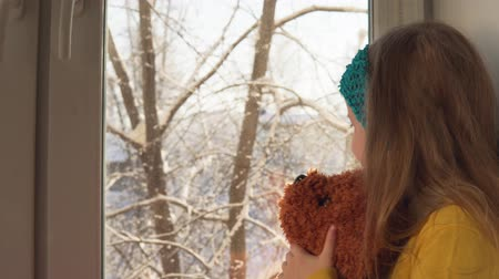 peluş : A cute little blonde girl with a blue bandage looks out the window at the winter landscape, sitting on the windowsill. Happy baby playing with a plush brown toy, dolly shot.
