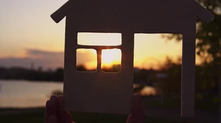 miniatűr : Close-up shot of hands holding a model of wooden house through door and window of which setting sun is visible background of evening coast.