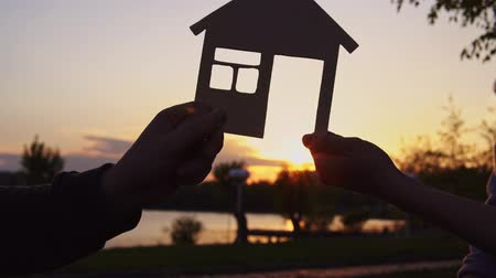 miniatűr : Close-up of realtor holding model of wooden house, man hands over pack of 100 dollar bills and gets keys to house against background of evening coast at sunset. Concept of buying or renting property.