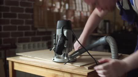 madeira compensada : Blond carpenter works with modern handheld plunge router with dust extraction tube in workshop. Strong joiner cuts round detail of furniture out of plywood.