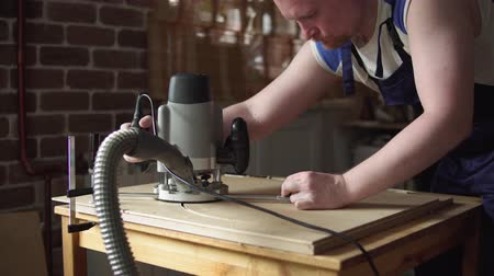madeira compensada : Blond carpenter works with modern hand-held plunge router with dust extraction tube in workshop. Joiner cuts round detail of furniture out of plywood.