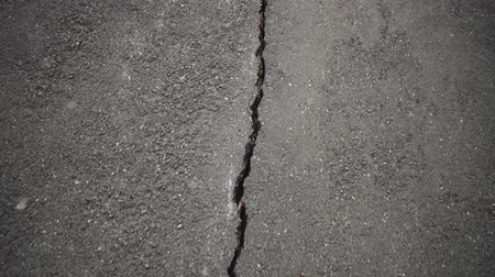 erozyon : Camera moves along deep cracks in asphalt. View of fault in road, consequences of natural disaster, earthquake or man-made disaster. Stok Video