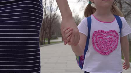 notas : Mother and daughter with backpack behind back rush to beginning of lessons. Young woman and pupil of primary school go hand in hand. Stock Footage