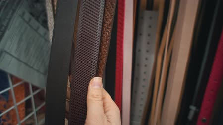 lederwaren : Close-up of a hand that touches multicolored waist-belts hung in a self-service store. Man chooses and buying eco-leather belt in supermarket. Stockvideo