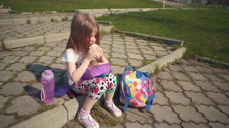 frasco pequeno : Blonde little girl eating lunch in park on sunny day.She holds reusable container of food on her lap, next to colorful backpack and bottle of water. Happy child sitting on step and bites off sandwich.