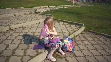 a small bottle : Blonde little girl eating lunch in park on sunny day.She holds reusable container of food on her lap, next to colorful backpack and bottle of water. Happy child sitting on step and bites off shawarma. Stock Footage