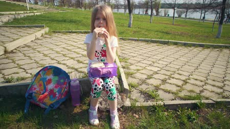a small bottle : Blonde little girl eating lunch in park on sunny day.She holds reusable container of food on her lap, next to colorful backpack and bottle of water. Happy child sitting on step and bites off sandwich.