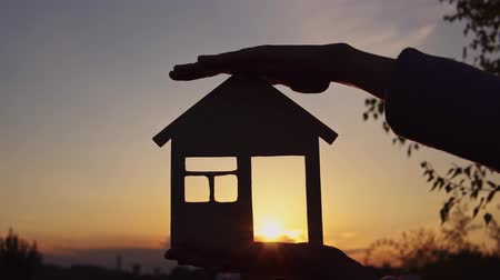 pancarte en bois : Close-ups shot of female hands holding a model of wooden house through door of which setting sun is visible. Vidéos Libres De Droits