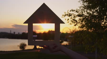 miniatűr : Close-ups shot of female hands holding a model of a wooden house through the window of which the setting sun is visible background of evening coast.