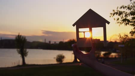mülkiyet : Close-ups shot of female hands holding a model of wooden house through door of which setting sun is visible background of evening coast.