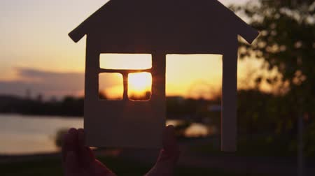 no hands : Close-ups shot of female hands holding a model of wooden house. Zooming in to get setting sun in window background of evening coast.