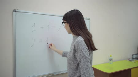 özel öğretmen : Female teacher stands at chalkboard and explains rules of addition in elementary school. Caucasian schoolmaster writes simple examples of sum of 1   1, 2   1 with black marker on whiteboard. Stok Video