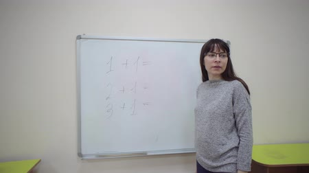 aritmética : Female teacher stands at whiteboard and explains rules of addition in elementary school. Stock Footage