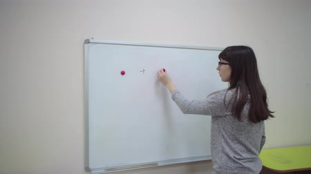 aritmética : Female teacher explains rules of addition in elementary school.Schoolmaster makes mathematical example on chalkboard, two red magnets through plus sign, then writes equal sign and number 2. Stock Footage