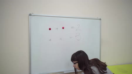 aritmética : Female teacher stands at whiteboard and explains rules of addition in elementary school. Caucasian schoolmaster in glasses makes mathematical examples using colored magnets and marker. Stock Footage
