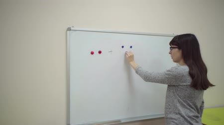 calcular : Female teacher explains rules of addition. Schoolmaster makes mathematical example on chalkboard, two red and three blue magnets through plus sign, then writes equal sign and number five. Vídeos