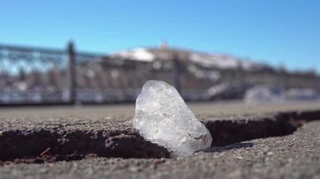 lasca : Close-up of a transparent small piece of ice melts in a crack of asphalt road under the bright sun on a warm spring day against a blue sky.