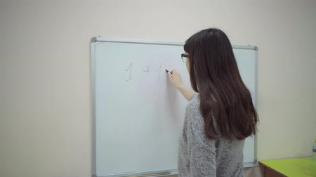 aritmética : Female teacher stands at whiteboard and explains rules of addition in elementary school. Caucasian schoolmaster in glasses writes with black marker on whiteboard simple example of sum of two units.