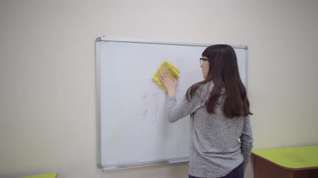 voorbeeld : Female teacher stands at whiteboard and explains rules of addition in elementary school. Caucasian schoolmaster in glasses removes the examples with a board duster.