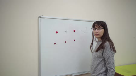 aritmética : Female teacher stands at whiteboard and explains rules of addition in elementary school. Caucasian schoolmaster in glasses makes mathematical examples using colored magnets and marker. Vídeos