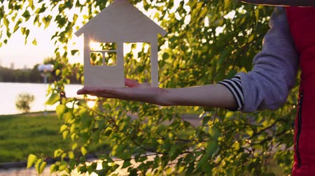 miniatűr : Close-ups shot of female hands holding model of wooden house through window of which the setting sun is visible on background of green leaves by pond. Concept of choosing place for new housing.