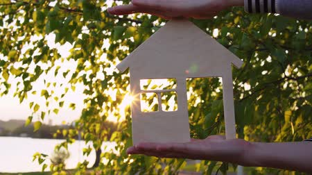 miniatűr : Close-ups shot of female hands holding model of wooden house through window of which the setting sun is visible on background of green leaves by sea.Concept of choosing place for new housing. Stock mozgókép