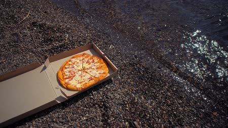 kiełbasa : Cardboard box with delicious, fresh, appetizing pizza on pebble beach, small waves roll ashore, space for text. Wideo