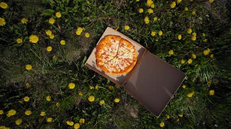kiełbasa : Camera spins around box with delicious, fresh, appetizing pizza in yellow dandelions, top view. Concept of summer fast food and rest.