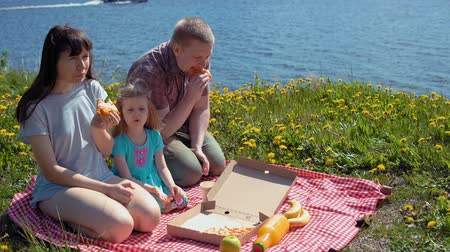 sea piece : Family of three, mom, dad and daughter, eat pizza together at picnic on beach among dandelions near sea on warm day.