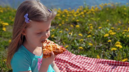 elvihető : Portrait of little cute girl in blue dress eats pizza sitting on red checkered blanket on glade with dandelions on seashore on warm day.