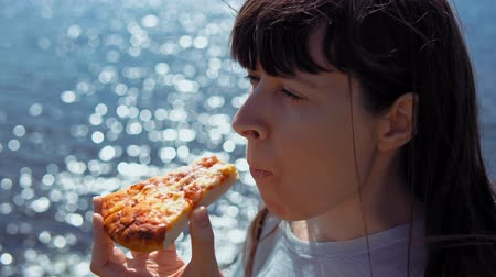 off shore : Close-up of young woman bites off piece of pizza and chews it on background of blue sparkling sea.
