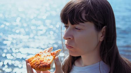 mastigação : Close-up of young woman bites off piece of pizza and chews it on background of blue sparkling sea.