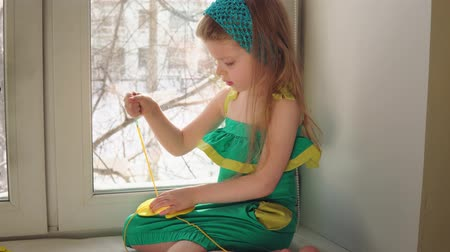 závit : Cute little girl sews a handbag. The child learns to use a needle and thread sitting on the windowsill.
