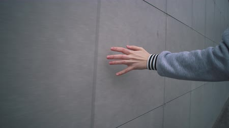 percepção : Closeup female hand touching gray wall of building. Girl walks next to greyish house and touches her surface with her hand.