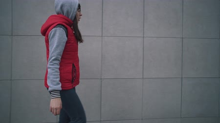 percepção : Young woman in red sleeveless jacket walks next to gray wall of building. Girl walks next to greyish house and touches her surface with her hand, handheld shoot. Stock Footage