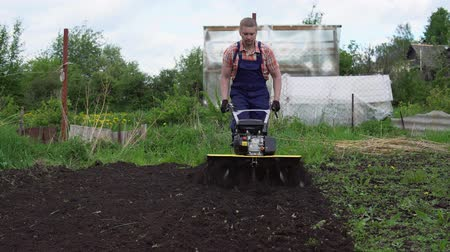 döner : Young blond muscular farmer cultivates ground soil with rotary mini tiller before planting in springtime, technology modern farming.