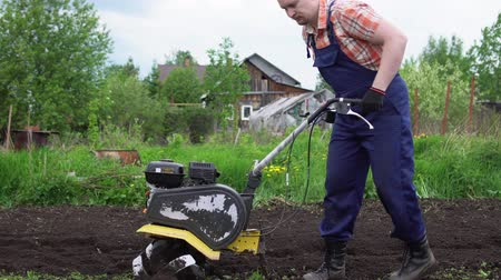 řezačka : Side view of young blond muscular farmer cultivates ground soil with rotary mini tiller before planting in springtime, technology modern farming.