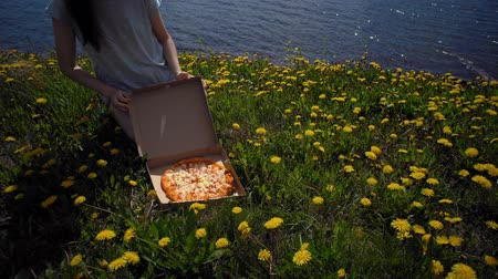 sea piece : Brunette girl opens the cardboard box with pizza on glade with dandelions on seacoast. Stock Footage