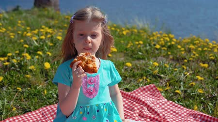 kayran : Portrait of little cute girl in blue dress eats pizza sitting on red checkered blanket on glade with dandelions on seashore on warm day.
