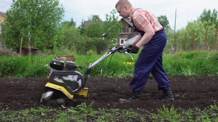 tiller : Side view of young blond muscular farmer cultivates ground soil with rotary mini tiller before planting in springtime, technology modern farming.