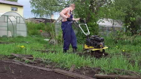 топливо : Side view of young blond muscular farmer cultivates ground soil with rotary mini tiller before planting in springtime, technology modern farming.